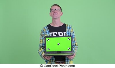 Portrait of happy nerd man thinking while showing laptop -...