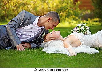 Portrait of happy newlyweds on grass