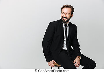 Portrait of happy office worker in black suit smiling while sitting on chair and looking aside on copyspace, isolated over white wall