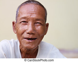 Portrait of happy senior Asian man with dental problems laughing and looking at camera against yellow wall