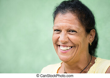 Portrait of happy old hispanic woman smiling at camera -...