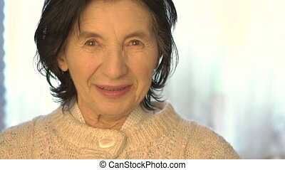 Portrait of happy old woman smiling on a camera on a bright background. Slowly