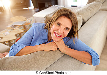 happy older woman relaxing at home on couch