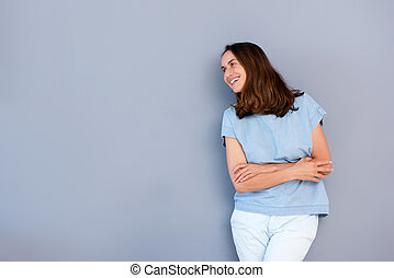 happy older woman smiling against gray background