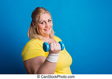 Portrait of happy overweight woman with dumbbell in studio...
