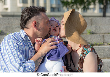 happy parents kissing their baby