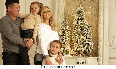 Portrait of happy parents with two daughters posing. Christmas photo session.