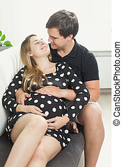 happy pregnant woman and man hugging on sofa at living room