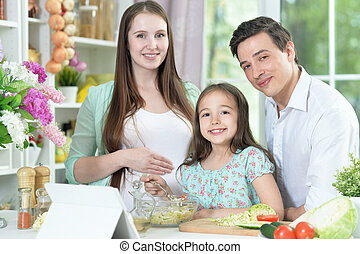 Portrait of happy pregnant woman with husband and daughter preparing salad together at kitchen