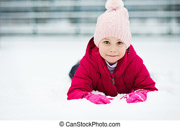 Portrait of happy pretty little girl plainf with snow in winter