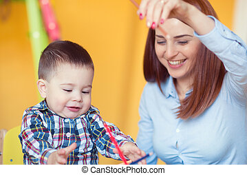 Portrait of happy pretty mother with her toddler son drawing