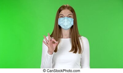 Portrait of happy pretty young girl in medical protective face mask looking at camera and showing ok sign with both hands. Redhead with long straight hair in a white blouse on a green screen in the studio. Health Protection Corona Virus Concept.