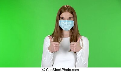 Portrait of happy pretty young girl in medical protective face mask looking at camera and showing thumbs up gesture with both hands. Redhead with long straight hair in a white blouse on a green screen in the studio. Health Protection Corona Virus Concept.