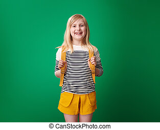 Portrait of happy pupil with backpack isolated on green
