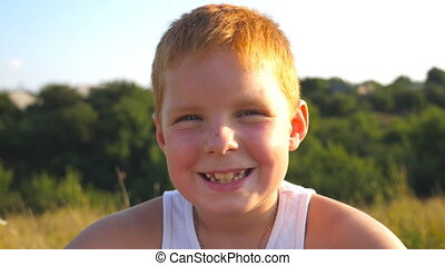 Portrait of happy red hair boy with freckles laughs outdoor. Adorable handsome baby looking into camera with joyful smile. Close up emotions of male child with glad expression on face. Slow motion