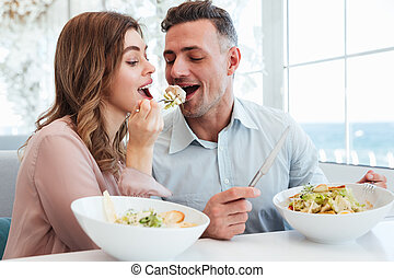 Portrait of happy romantic couple having dinner and eating salat together, while having lunch break in restaurant