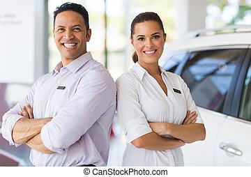 sales staff standing in vehicle showroom