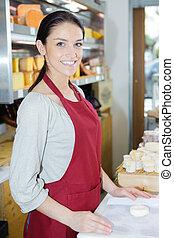 portrait of happy saleswoman in cheese shop