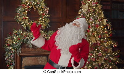 Portrait of happy Santa Claus in traditional costume dancing in decorated house