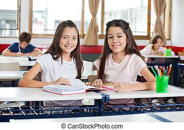 Portrait Of Happy Schoolgirls Sitting With Book At Desk