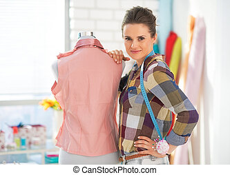 Portrait of happy seamstress with mannequin