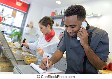 portrait of happy seller on call in butchery