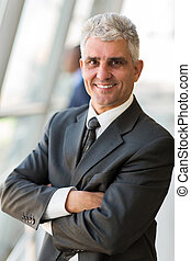 senior businessman with arms crossed - portrait of happy...