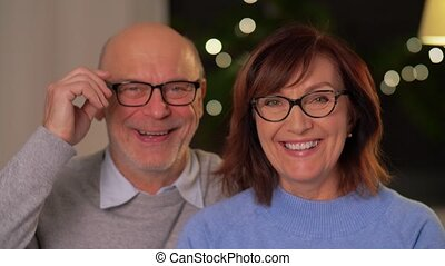 relationships, old age and people concept - portrait of happy smiling senior couple at home in evening