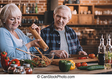 portrait of happy senior couple cooking together at home