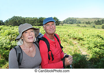 Portrait of happy senior couple hiking in natural landscape