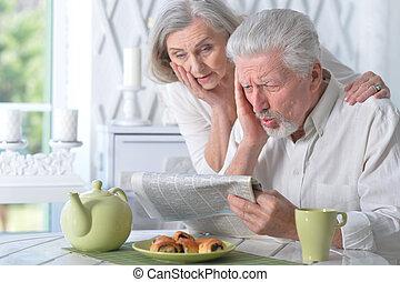 Portrait of happy senior couple reading newspaper