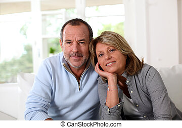 Portrait of happy senior couple sitting in sofa