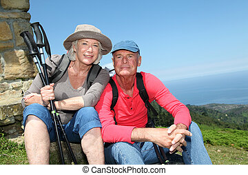 Portrait of happy senior hikers resting by stone house