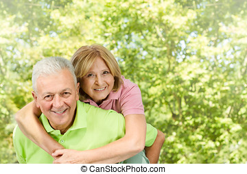 happy senior man giving piggyback ride mature woman