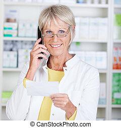 Portrait of happy senior pharmacist using cordless phone...