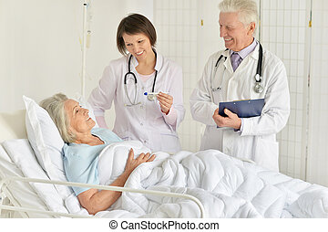Portrait of happy senior woman in hospital with caring doctors