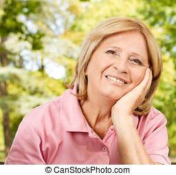 Portrait of happy senior woman in the park