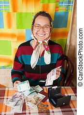 senior woman with money  at home