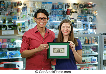 Portrait Of Happy Shop Owners Showing First Dollar Earning -...