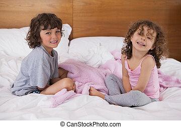 Portrait of happy siblings sitting in bed