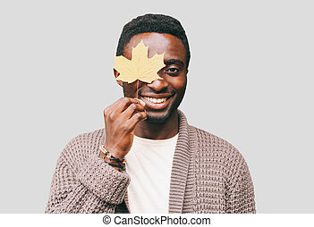 Portrait of happy smiling african man with autumn yellow maple leaves on a gray background
