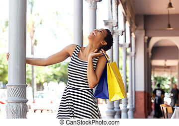 happy smiling african woman striped dress holding shopping bag