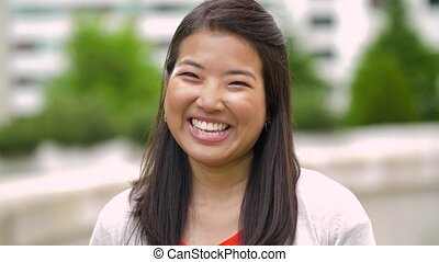 portrait of happy smiling asian woman outdoors - race,...