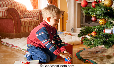 Portrait of happy smiling boy taking toys of Christmas gift box and playing on floor under Christmas tree