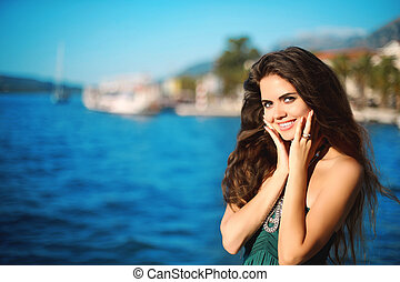 Portrait of happy smiling brunette woman with long wavy hair thinking