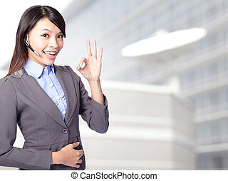 Portrait of happy smiling cheerful female customer support phone operator in headset showing okay gesture at office, asian woman