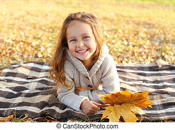 Portrait of happy smiling child lying on plaid with yellow maple leafs in autumn park