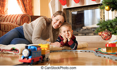 Portrait of happy smiling family lying on floor and looking at train riding on railroad under Christmas tree at living room