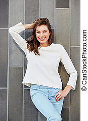 happy smiling female fashion model posing against a wall