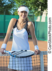 Portrait of Happy Smiling Female Tennis Player at Court Standing Close To the Net. Vertical Image
